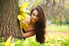 Pretty girl hiding behind a tree Stock Photography