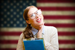 Pretty girl in hipster glasses smiling on USA flag Royalty Free Stock Images