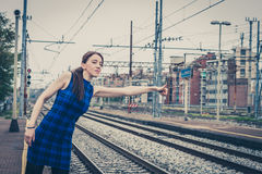 Pretty girl hitchhiking along the tracks Stock Image