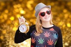 Pretty girl holding alarm clock on golden bokeh Stock Image