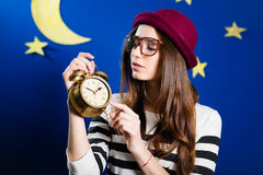 Pretty girl holding alarm-clock on paper stars and Royalty Free Stock Photo