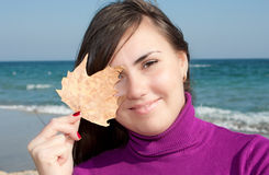 Pretty girl holding an autumn leave. Pretty smiling girl holding an autumn leave royalty free stock image