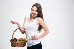 Pretty girl holding basket with fruits. Portrait of a smiling pretty girl holding basket with fruits isolated on a white background Royalty Free Stock Photos