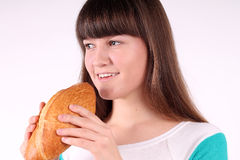 Pretty girl holding and biting loaf of bread Stock Images