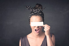 Pretty girl holding blank copy space paper at her eyes Stock Images