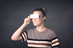 Pretty girl holding blank copy space paper at her eyes Royalty Free Stock Images