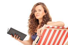 Pretty girl holding a book seated on sun lounger Stock Images