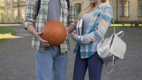 Pretty girl holding books and chatting with athletic man near college, flirt. Stock footage stock footage