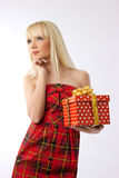 Pretty girl holding christmas gift in red dress Royalty Free Stock Images