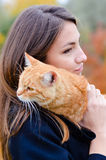 Pretty girl holding cute red kitten on blurred stock images