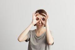 Pretty girl holding fingers near eyes like glasses Stock Photos