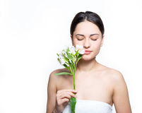 Pretty girl holding a flower near the face and inhales its fragr Royalty Free Stock Photos