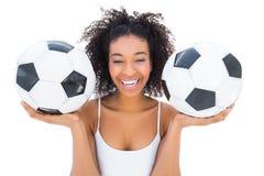 Pretty girl holding footballs and laughing at camera Stock Photos