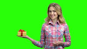 Pretty girl holding gift box on green screen. Young smiling woman in casual wear pointing with finger on gift box. Get your bonus concept stock video footage