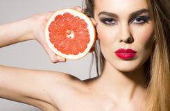 Pretty girl holding grapefruit cut in half next to the head Royalty Free Stock Photo