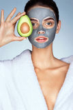 Pretty girl holding half an avocado in front of her face. Royalty Free Stock Photo