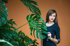 Pretty girl holding by hand stalk of palm Royalty Free Stock Image