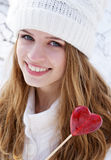Pretty girl holding a heart candy Royalty Free Stock Images