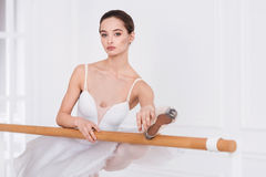 Pretty girl holding her leg on the ballet bar Royalty Free Stock Photo