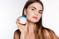 Pretty girl is holding jar of face cream Royalty Free Stock Photos