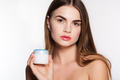 Pretty girl is holding jar of face cream Stock Images