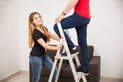 Pretty girl holding a ladder Royalty Free Stock Images