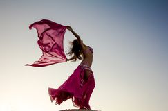 Pretty girl holding pink cloth in wind with sky Royalty Free Stock Photography