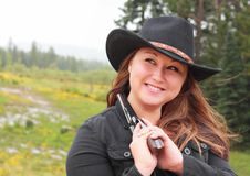 Pretty Girl Holding Revolver in Rain. Photo of a pretty cowgirl in black cowboy hat holding a revolver while it is raining Stock Photography