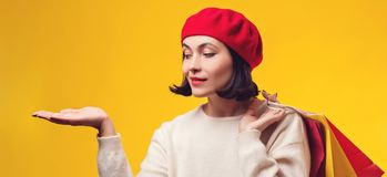 Pretty girl holding shopping bags. Woman in red hat with presentation. Girl showing your product with open hand palm. Shopping. Woman isolated on yellow stock photography