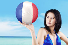 Pretty girl holds ball on the coast Royalty Free Stock Photos