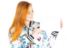 Pretty girl holds blank board and looks at her. Redheaded girl w Royalty Free Stock Photo