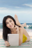 Pretty girl holds tablet at shore. Portrait of a pretty girl dreaming something while holding a digital tablet and lying on the beach Stock Images