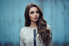 Pretty girl in hoodie against blue wall Royalty Free Stock Images