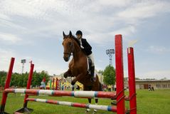 Pretty girl horse jump. Equestrian and audience Stock Photo