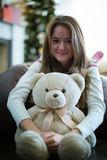 Pretty girl hugs teddy bear. Christmas time. Royalty Free Stock Image