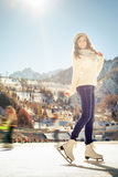 Pretty girl ice skating outdoor at ice rink Stock Photography