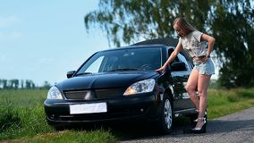 Pretty girl inflating car tyre with foot pump stock footage