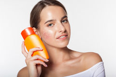 Pretty girl with jar of sunscreen lotion. Studio portrait of beautiful natural girl is holding sunscreen tanning lotion jar in hands and sun shape cream on her Stock Photo
