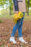 Pretty girl in jeans and coat with bright colored leaves walking in autumn park stock photos