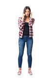 Pretty girl in jeans and sneakers talking on the mobile phone adjusting hair Royalty Free Stock Images