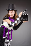 Pretty girl in jester costume holding clapperboard Royalty Free Stock Images