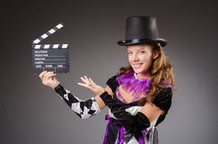 Pretty girl in jester costume holding clapperboard Stock Photo
