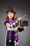 Pretty girl in jester costume holding clapperboard Royalty Free Stock Photography