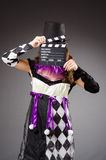 Pretty girl in jester costume holding clapperboard Stock Photography