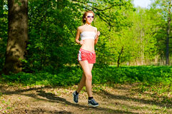 Pretty girl jogging in summer forest Stock Images