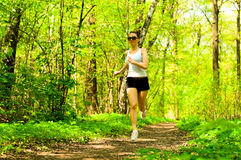 Pretty girl jogging in summer forest Royalty Free Stock Photography