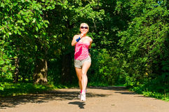 Pretty girl jogging in summer forest Royalty Free Stock Images