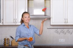 Pretty girl juggles bell pepper Stock Images