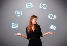 Pretty girl juggling with elecrtonic devices icons Stock Photography