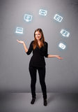 Pretty girl juggling with elecrtonic devices icons Royalty Free Stock Photo